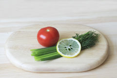 Red tomato, green onion, dill, lemon on a cutting Board Stock Photography