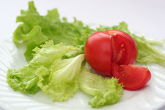 Red tomato, green salad. Red tomato and green salad on a white plate Stock Photography