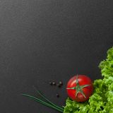 Red tomato with green salad on black Stock Photos