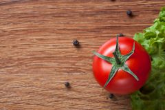 Red tomato with green salad on wood Royalty Free Stock Images