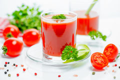 Red tomato juice in transparent glasses with parsley, cutted tom Royalty Free Stock Photography