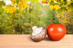 Red tomato and mushroom on a wooden table Stock Photos