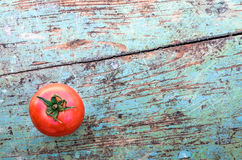 Red Tomato on Old Rustic Table Top Stock Image