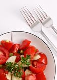 Red tomato and parsley salad with silver forks Stock Photos
