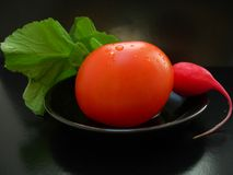 The red tomato with radish on a black plate Stock Image