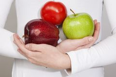 Red tomato, red apple, red applein woman hands Royalty Free Stock Photo