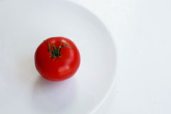 Red tomato on a round plate over white Stock Image