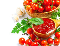 Red tomato sauce. In a wooden spoon and ingredients, isolated in white Stock Photo