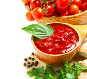 Red tomato sauce. In a wooden spoon and ingredients, isolated in white Stock Image