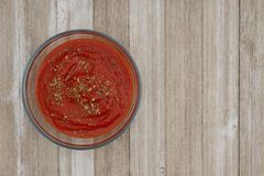 Red tomato sauce in clear bowl on weathered wood background royalty free stock images