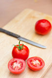 Red tomato with slice on wood board Royalty Free Stock Photography