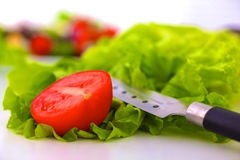 Red tomato slices and knife on chopping board.  Stock Photos