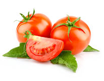 Red tomato vegetable with cut and green leaves Stock Photos