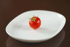 Red tomato on white oval plate. Red tomato with green stem and water drops on white oval plate with reflection Royalty Free Stock Photography