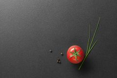 Red Tomato With Green Onion On Black Royalty Free Stock Image