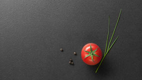Red Tomato With Green Onion On Black Stock Photos