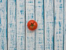 Red tomato on a wooden table. Fresh red tomato lies on a wooden table Stock Photography