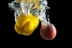 Red tomato and yellow pepper in water on black background Royalty Free Stock Images