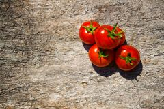 Red tomatoes. On a wooden table royalty free stock photo