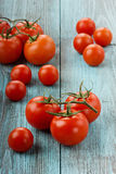 Red tomatoes. On a turquoise colored wooden surface Royalty Free Stock Photo