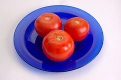 Red tomatoes. Three red tomatoes on a plate Stock Photography