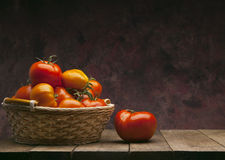 Red tomatoes in basket on dark background Stock Image