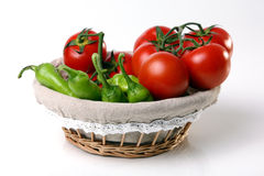 Red tomatoes in basket with green. Red tomatoes and green peperoni in basket on white background Stock Photos