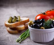 Red tomatoes, black and green olives in white bowl on jute fabric Royalty Free Stock Image