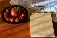 Red tomatoes in a black plate on the kitchen table next to a Notepad stock photo
