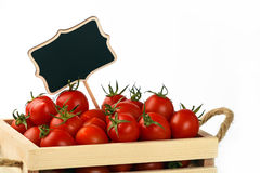 Red tomatoes in box with price sign over white Royalty Free Stock Images