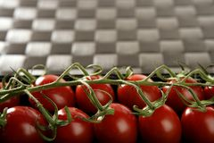 Red tomatoes branch. Un a black plastic box over brown tablecloth royalty free stock photo