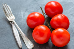Red tomatoes on a branch, fork and knife. Stock Photography