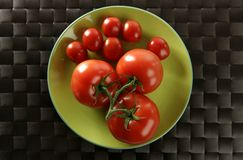 Red tomatoes branch, little an big tomatoes. Over green plate stock image