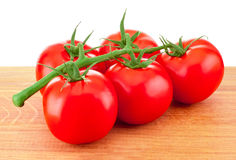 Red tomatoes on branch on wooden board Royalty Free Stock Image