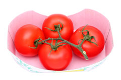 Red tomatoes. Bunch of red tomatoes in a cardboard box, on white background Stock Photos