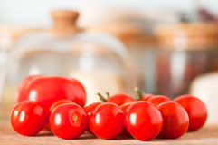 Red tomatoes with cheese under glass in background. Big ripe red tomato and small cherry tomatoes with cheese under glass dome in blurry background. Shallow Royalty Free Stock Images