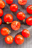 Red  tomatoes cherry on dark wooden board,top view Royalty Free Stock Image