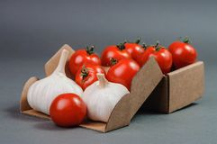 Red tomatoes and couple of garlic. Some red tomatoes and couple of garlic in the box stock images