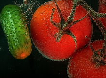 Red tomatoes and cucumber with air bubble on a surface on a blac Royalty Free Stock Images