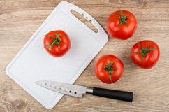 Red tomatoes, cutting board and kitchen knife on table Stock Photos