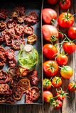 Red tomatoes dried in the sun on baking tray. On wooden table royalty free stock photography
