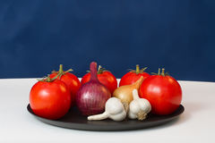 Red tomatoes, garlic  and onions. On a table Royalty Free Stock Photos