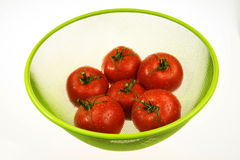 Red tomatoes in green basket. Six red tomatoes in green basket on white isolated background.Tomatoes dewy drops of water.Horizontal view Stock Photography