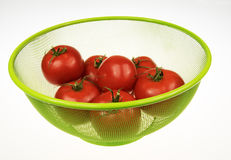 Red tomatoes in green basket. Six red tomatoes in green basket on white isolated background.Horizontal view Royalty Free Stock Photo