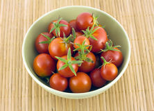 Red tomatoes in green bowl on straw mat Royalty Free Stock Images
