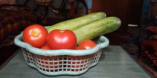 The fresh tomatoes and cucumbers are placed on the table. stock photo