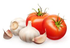 Red tomatoes with green leaves and garlic with cloves Royalty Free Stock Images