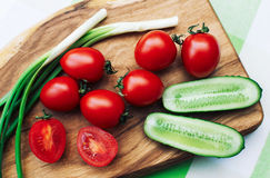 Red tomatoes and green onions on cutting board Stock Images