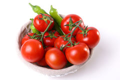 Red tomatoes and green peperoni. In basket on white background Stock Photo