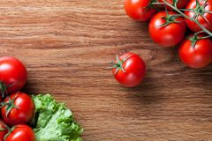 Red tomatoes with green salad on wood Stock Images